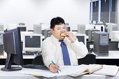 stock photo of grease  - Obesity businessman working in office while eating junk food - JPG