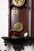 stock photo of pendulum clock  - Glass of brandy standing inside an old clock - JPG