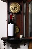 pic of pendulum clock  - Bottle of red wine with blank label template standing inside an old clock - JPG