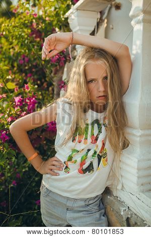 The portrait young girl about 9-12 years old with the blonde and loose hair that stands near