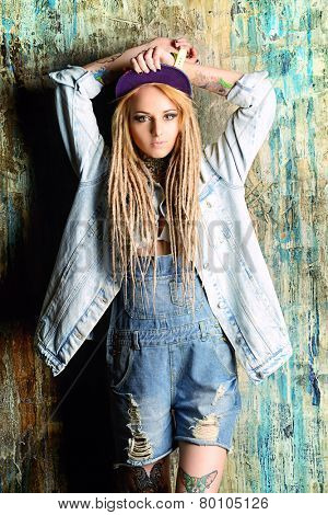 Modern teenage girl with blonde dreadlocks. Jeans style. Modern generation.