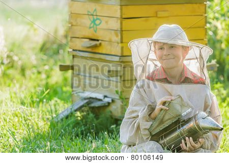 Teenage beekeeper with painted wooden beehives
