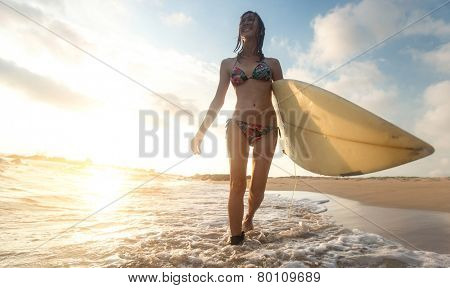 Surfer girl walking with board on the sandy beach