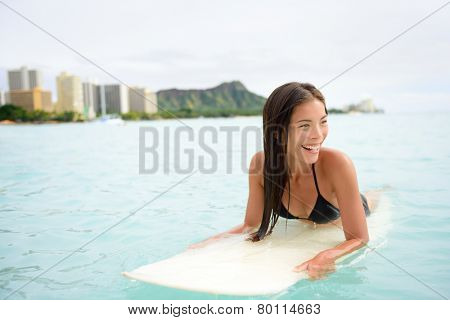 Surfer woman surfing on Waikiki Beach, Oahu, Hawaii. Female bikini girl on surfboard smiling happy living healthy active lifestyle on Hawaiian beach. Asian Caucasian model.