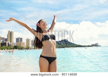 Beach woman in bikini happy and free on Waikiki, Oahu, Hawaii, USA. Girl on travel vacation holidays having fun on Hawaiian Waikiki beach with Diamond Head mountain. Asian Caucasian model.