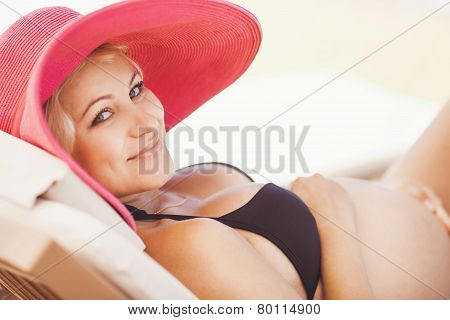 Pregnant woman sunbathing on the beach.