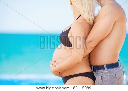 Hands of men and women on the abdomen of a pregnant wife.