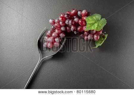Wine glass made of forks and grape on black background