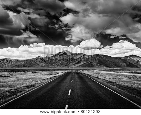 Travel forward concept background - road on plains in Himalayas with mountains and dramatic clouds. Manali-Leh road, Ladakh, Jammu and Kashmir, India. Black and white version
