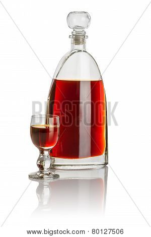 Carafe and glass goblet filled with brown liquid