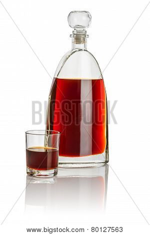 Carafe and drinking glass filled with brown liquid