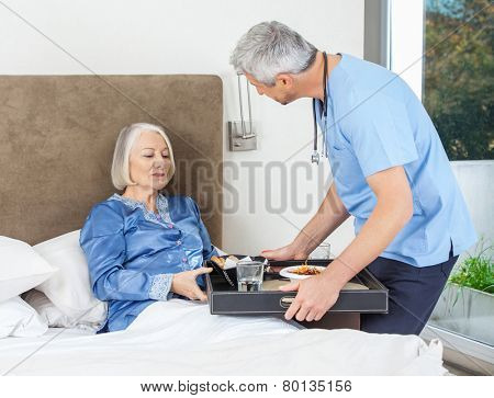 Male nurse serving breakfast to senior woman on bed in nursing home
