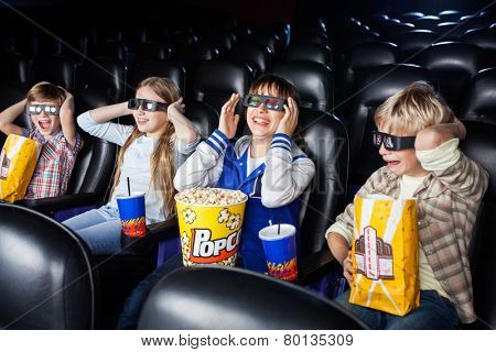Brothers and sisters enjoying 3D movie in cinema theater
