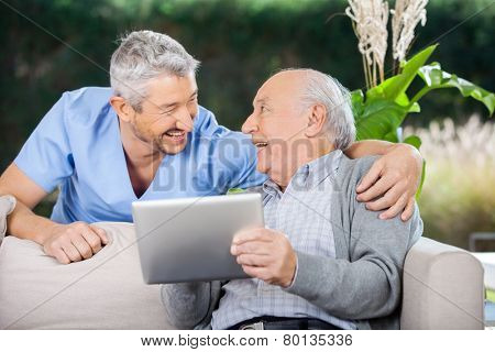 Laughing male caretaker and senior man using tablet computer at nursing home porch