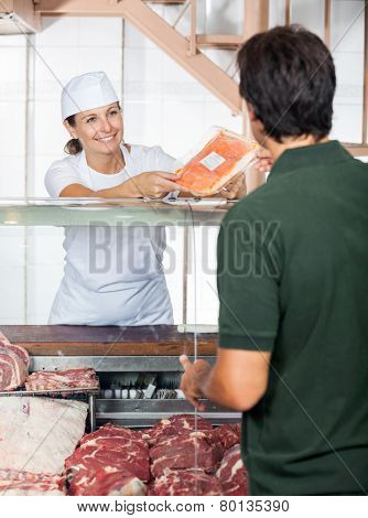 Happy female butcher selling fresh meat to male customer at butchery