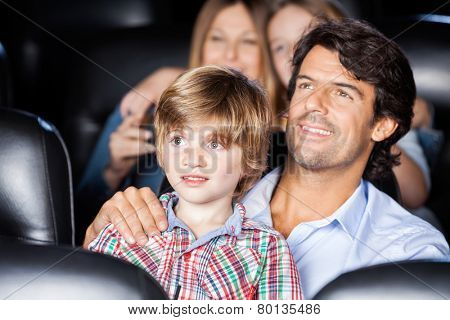 Father and son watching film with family in movie theater