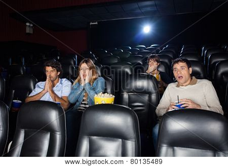 Shocked people watching film in movie theater