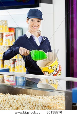 Portrait of smiling female worker pouring popcorn in bucket at cinema concession stand