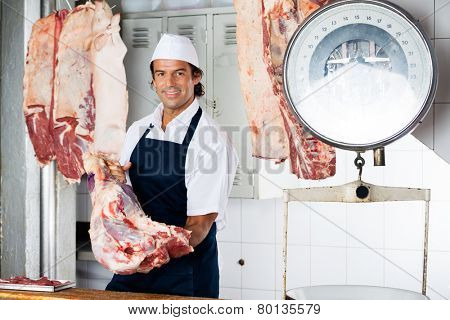 Portrait of confident butcher holding raw meat in shop