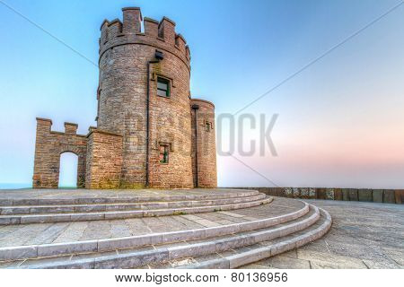 Castle tower on Irish Cliffs of Moher at sunset