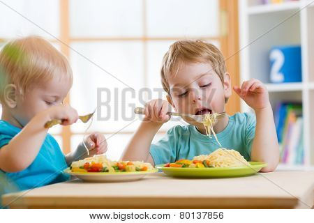 kids eating healthy food in kindergarten or nursery