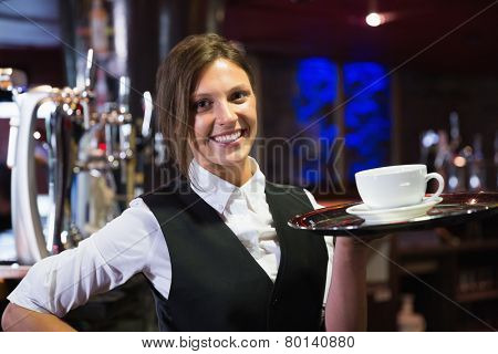 Happy barmaid holding tray with coffee in a bar