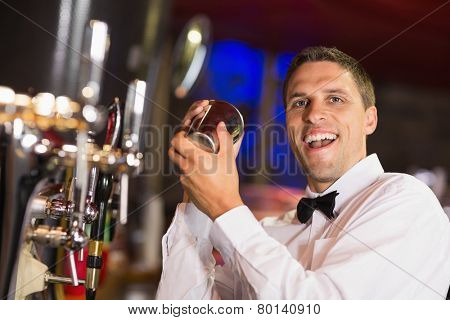 Handsome barman smiling at camera making a cocktail in a bar