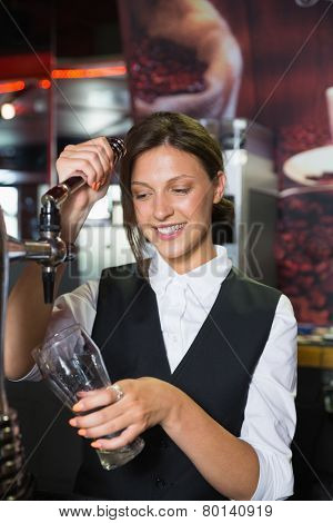 Happy barmaid pulling a pint of beer in a bar
