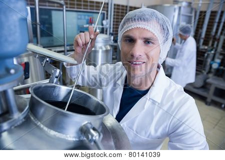 Smiling scientist using brewer in the container in the factory