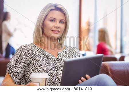 Smiling woman using digital tablet and holding disposable cup in library