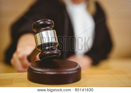 Hand about to bang gavel on sounding block in the court room
