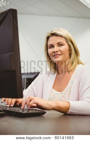 Mature student using laptop looking at camera in the office