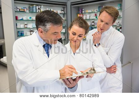 Team of pharmacists looking at clipboard at the hospital pharmacy