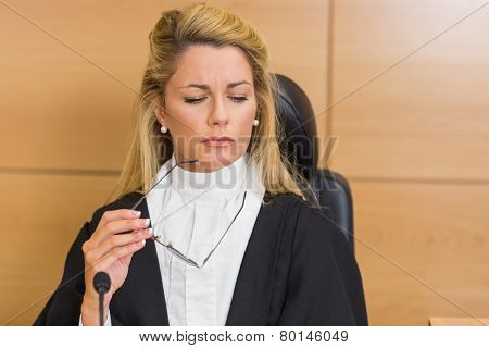 Stern judge looking and listening in the court room