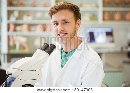 Young scientist working with microscope at the university