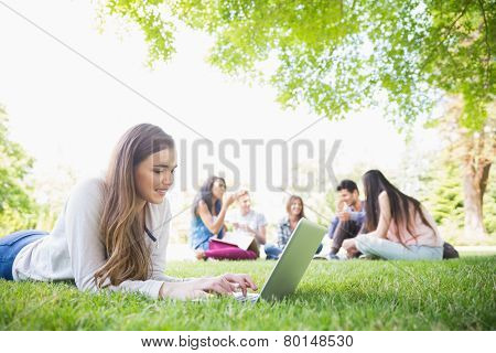 Happy student using her laptop outside at the university