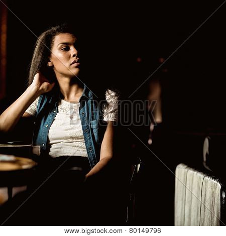 Pretty student sitting alone and thinking in a pub
