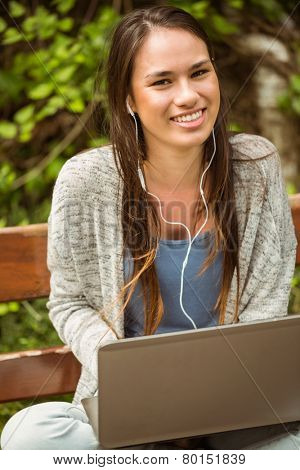 Smiling student sitting on bench listening music and holding laptop in park at school