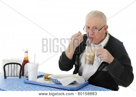 A senior adult man enjoying a meal of hamburger, fries, and a root beer float.  On a white background with space for your text over his drink and the ketchup.