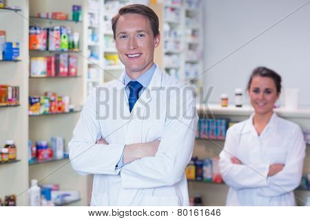 Pharmacist with his trainee standing with arms crossed in the pharmacy