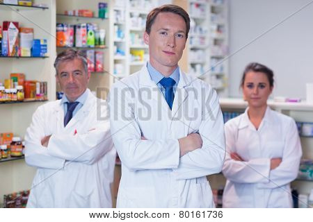 Smiling pharmacy team standing with arms folded in the pharmacy
