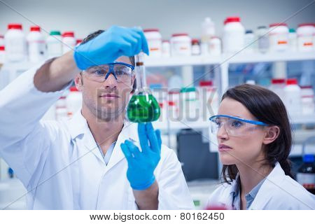 Chemist team looking beaker of green chemical in the laboratory
