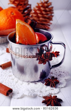 Metal mug of mulled wine on lace doily with orange and spice on color wooden background