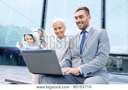 business, communication, technology and people concept - smiling businesspeople making video call or conference with laptop computer on city street