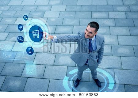 business, sale, technology and people concept - young smiling businessman pointing finger to shopping trolley icon on virtual screen outdoors from top