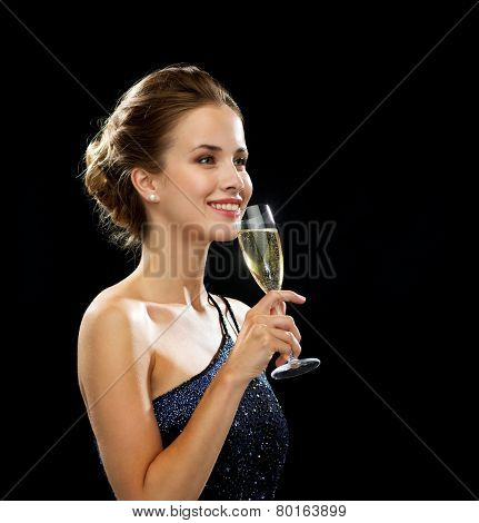 party, drinks, holidays, luxury and celebration concept - smiling woman in evening dress with glass of sparkling wine over black background