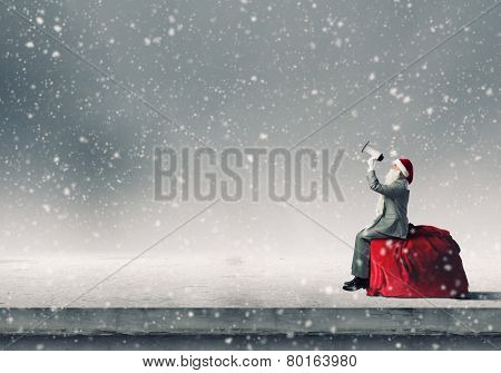 Businessman in Santa costume shouting in megaphone