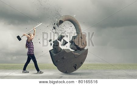 Cute little girl crushing stone lock with hammer