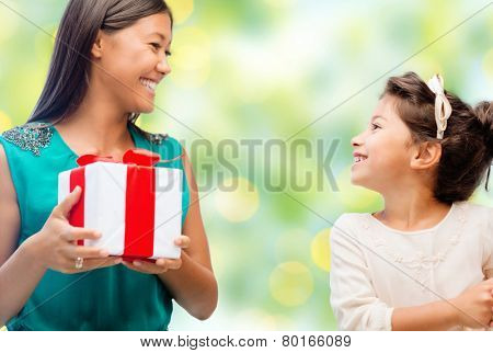 people, holidays, christmas and family concept - happy mother and daughter with gift box over green lights background