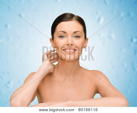 beauty, people and health concept - smiling young woman with bare shoulders over blue wet background